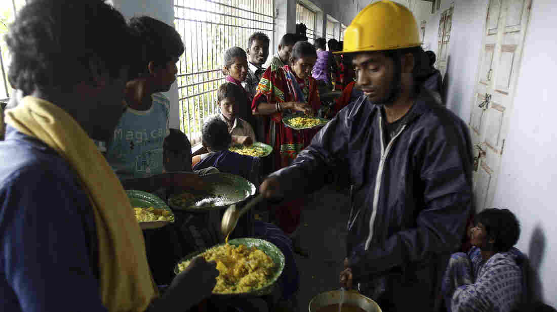Villagers eat at a temporary cyclone shelter in Chatrapur, India, on Saturday. India evacuated ne