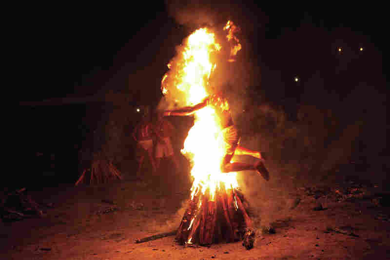After working himself into a trance, a man leaps through a flaming pyre.