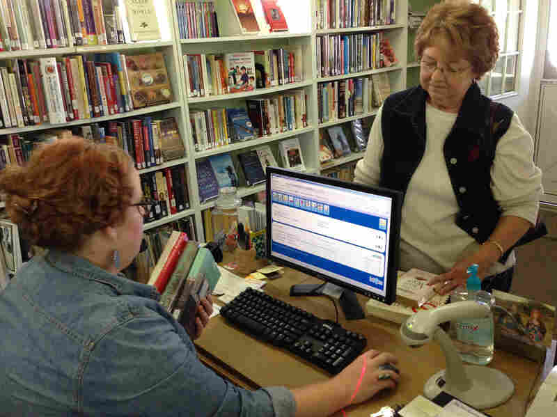 Luster checks out books for frequent library visitor Phyllis Smith. Luster says she thinks of herself as a book curator.