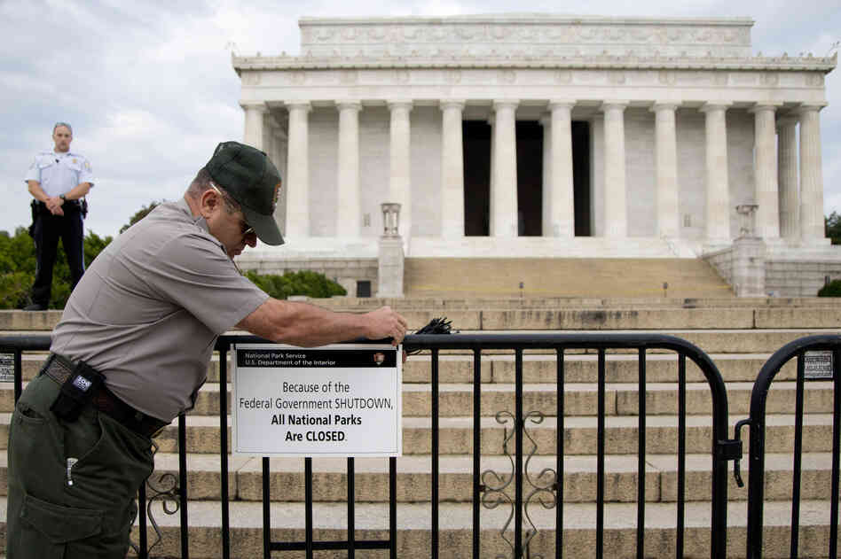 A National Park Service employee posts a sign on a barricade in front of the Lincoln Memorial in Washington, D.C., on Oct. 1, the first day of the U.S. government shutdown.