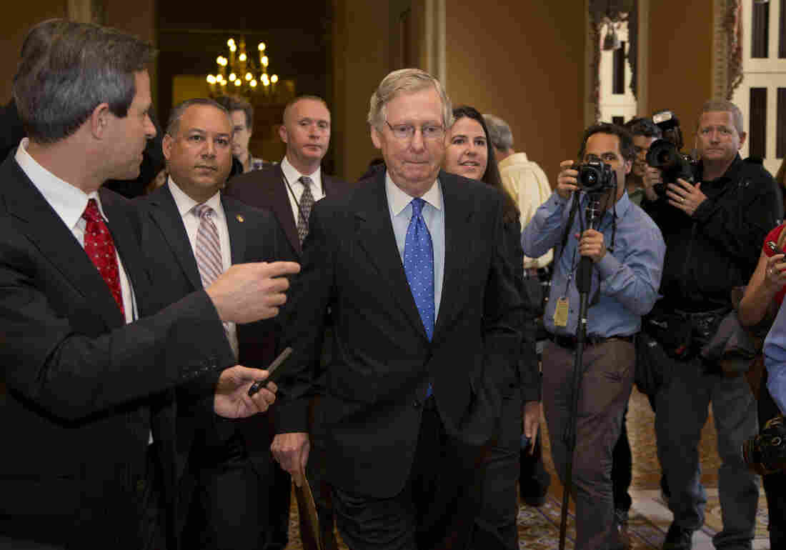 Senate Minority Leader Sen. Mitch McConnell, R-Ky., walks to the Senate floor after agreeing to the framework of a deal to avoid default and reopen the government, on Capitol Hill on Wednesday.