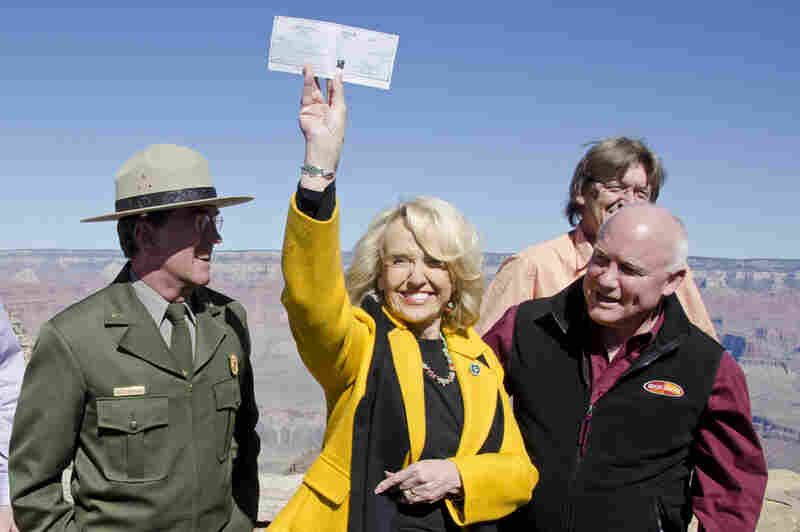 Arizona Gov. Jan Brewer holds a check for $426,500, presented to her by the town of Tusayan, Ariz., as partial payment to open Grand Canyon National Park. The National Park Service announced that it entered into an agreement with the state of Arizona that would allow the park to re-open and temporarily operate during the shutdown.