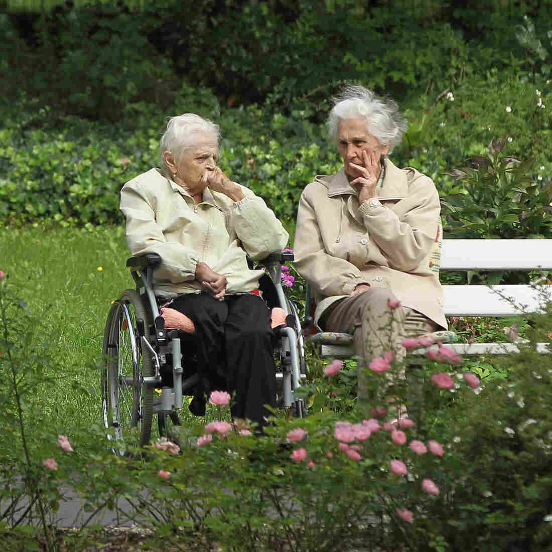 """Two German women chat in the gardens of a senior care home in Berlin. Germany is grappling with a rapidly aging population: By 2050, almost a third of Germans will be 65 years or older, and a growing """"Grandma export"""" trend has set hands wringing."""