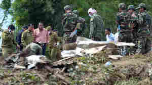 Soldiers stand next to pieces of a Lao Airlines plane on Thursday after it crashed into the Mekong River near Pakse, Laos.
