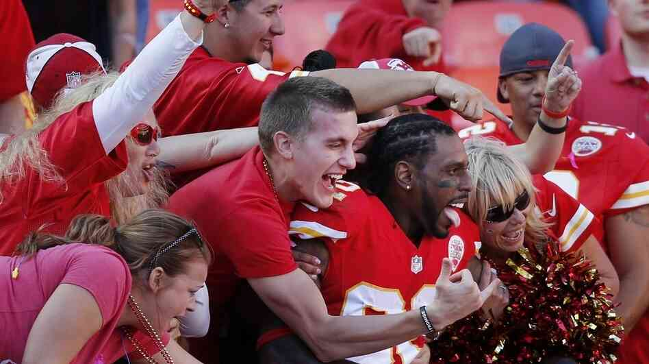 Fans cheer wildly with a Kansas City Chiefs player at an NFL game against the Oakland Raiders. For many fans, the risky side of football doesn't quell their love of the sport.
