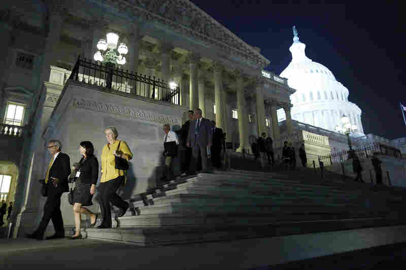 Members of the House of Representatives depart after a late-night vote Wednesday on legislation to raise the debt ceiling and end the government shutdown. President Obama signed the bill just after midnight.