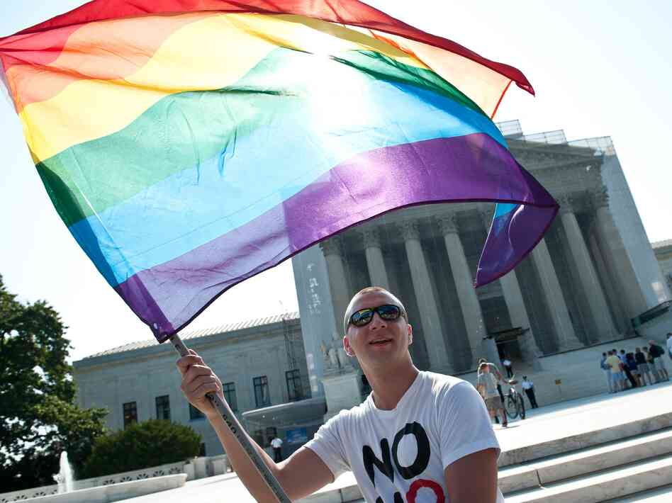A gay rights activist waves a rainbow flag in front of the U.S. Supreme Court
