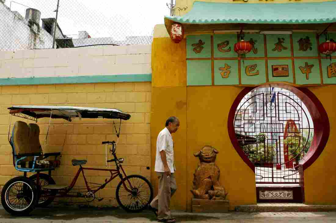 An unidentified Chinese man walks past a Cuban bicycle taxi and the main entrance of the Cuban Wushu Association of Havana's Chinatown on May 23, 2006. Fewer than 150 elderly Chinese immigrants remain in Havana. The Chinese presence in Cuba dates back to 1847, when a group of 200 immigrants from Canton province arrived on a Spanish ship to work on the island's sugarcane plantations.