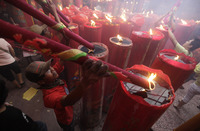 A worker burns large incense sticks during the celebration of the Lunar New Year of the Tiger at a temple in the Chinatown in Jakarta, Indonesia, on Feb. 14, 2010.