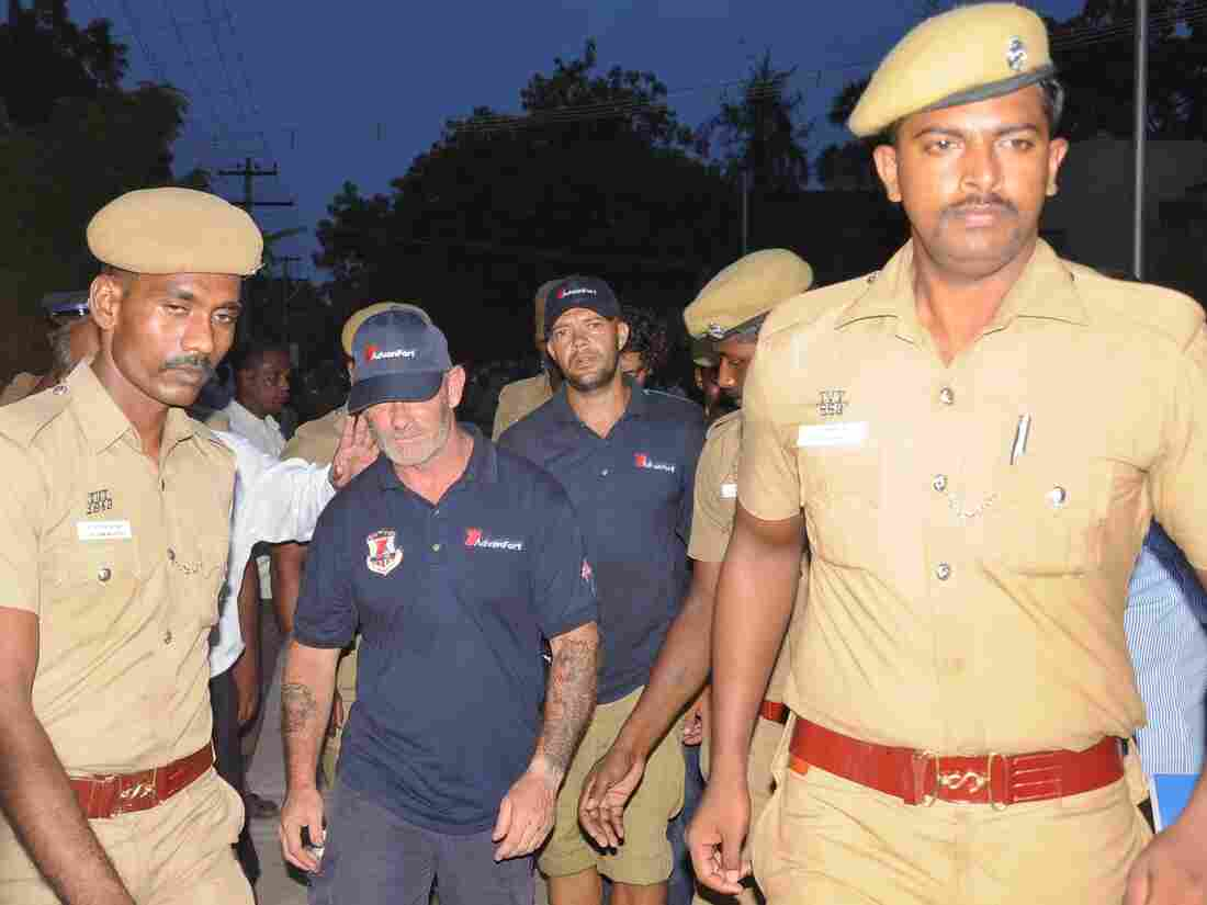 Indian policemen escort crew members of a U.S.-owned ship MV Seaman Guard Ohio outside a court in Tuticorin, in the southern Indian state of Tamil Nadu, on Friday.