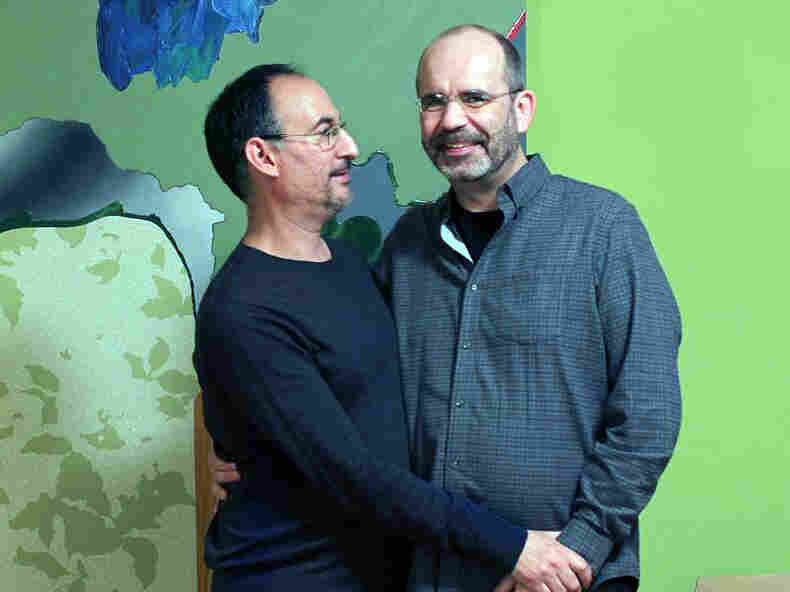 David Lozano (left) and Kevin Kreinbring stand in front of a painting created by Lozano. The couple says they get tested for HIV together every six months.