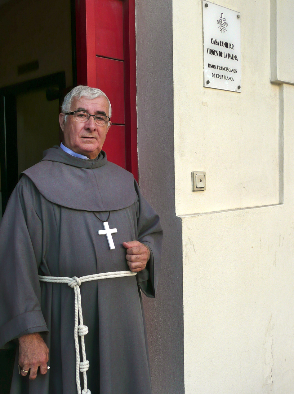 "Isidoro Macías Martín, aka ""Padre Patera,"" stands in front of his monastery office across the street from the port of Algeciras, in southern Spain. Martín is a Franciscan brother who for 40 years has been the first point of contact in Spain for thousands of Africans arriving illegally by boat."