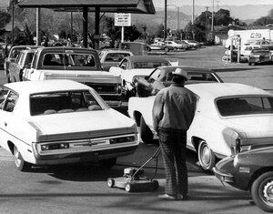 Drivers and a man pushing a lawnmower line up a