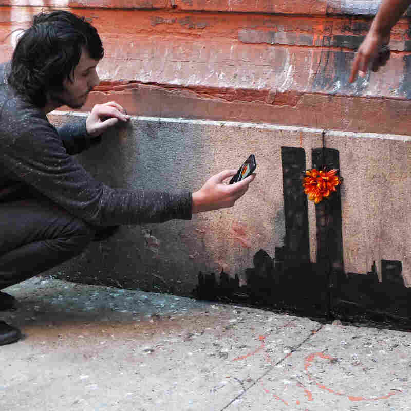 A man takes a photograph while another poses in front of Banksy's latest work depicting a pre-Sep. 11 New York City skyline.