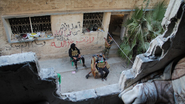 Syrian opposition fighters sit on the front line in the city of Deir Ezzor on Oct. 13. Ongoing violence has ravaged the city since March 2011.
