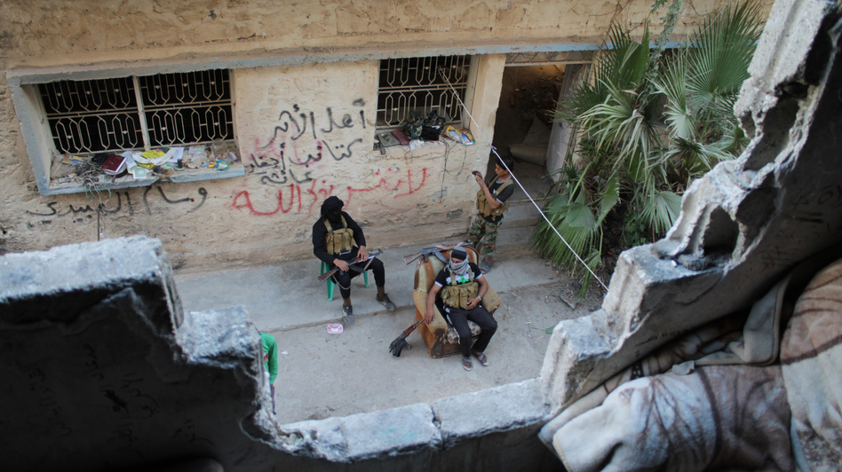 Syrian opposition fighters sit on the front line in the city of Deir Ezzor on Oct. 13. Ongoing violence has ravaged the city since March 2011. (AFP/Getty Images)