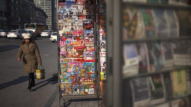 A woman walks past a newsstand in Beijing.