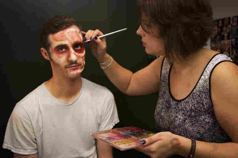 At one of 14 makeup stations, Nickki Duban works on Josh Rothstein's stitches. All of the masks are created in house and the makeup artists look to images of gruesome injuries and half-human creatures for inspiration.