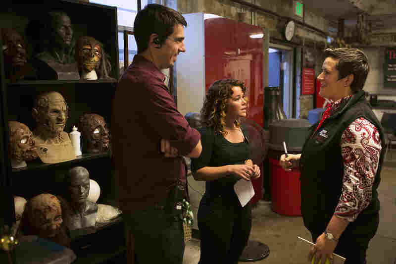 "Stage manager Ed Rafter and human relations manager Molly McGoey meet with creative director Amy Hollaman (right) before the opening of ""Terror Behind The Walls."" Hollaman works for both the historical society and the haunted attraction."
