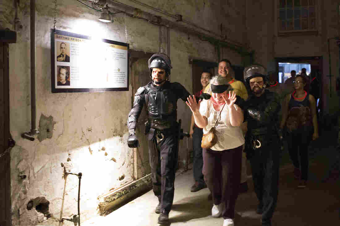 "Sue Sawyer is escorted by the Zombie SWAT team through a cellblock. Her family follows close behind — but will soon be prevented from going any farther. Sawyer elected to wear a glow necklace, indicating she's up for a scare and proving true the old saying, ""You get what you pay for."""