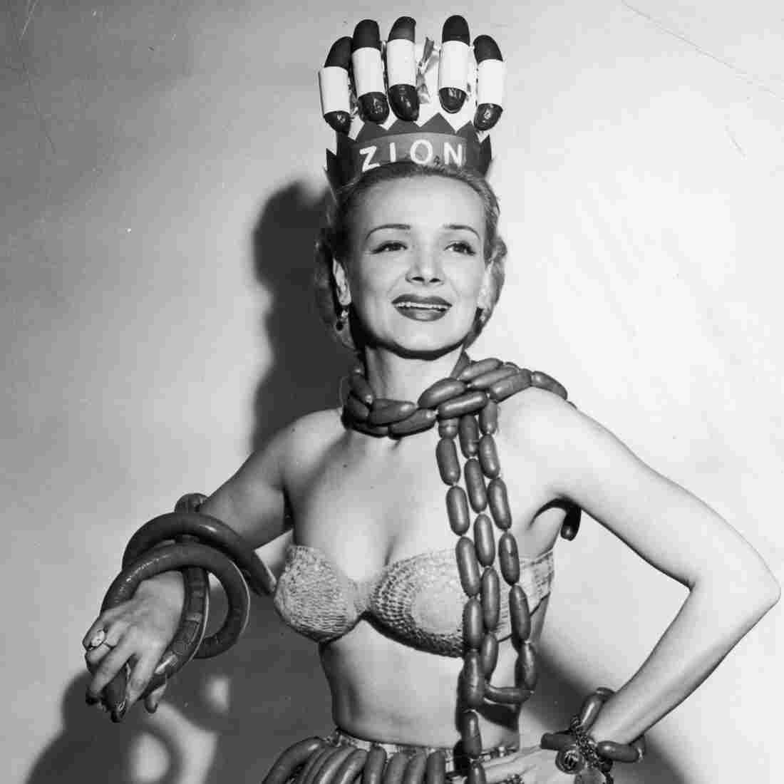 Geene Courtney models a scarf, skirt, bracelets and a crown made from hot dogs, frankfurters and kielbasa in her role as Queen of National Hot Dog Week, circa 1955.