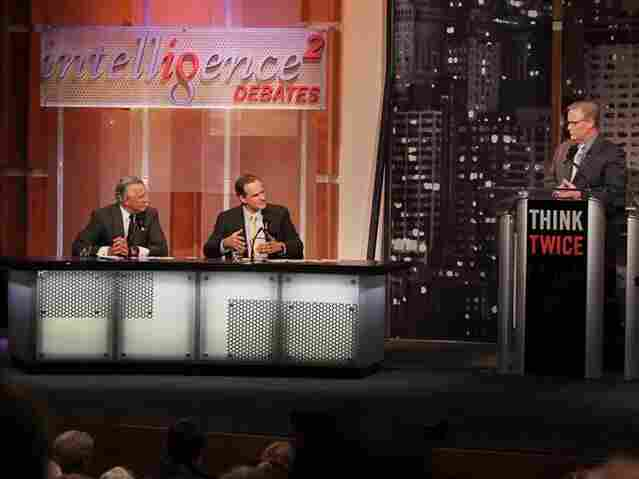 Richard Fisher (left) and Simon Johnson argue in favor of breaking up big banks in an Intelligence Squared U.S. debate, as moderator John Donvan looks on.