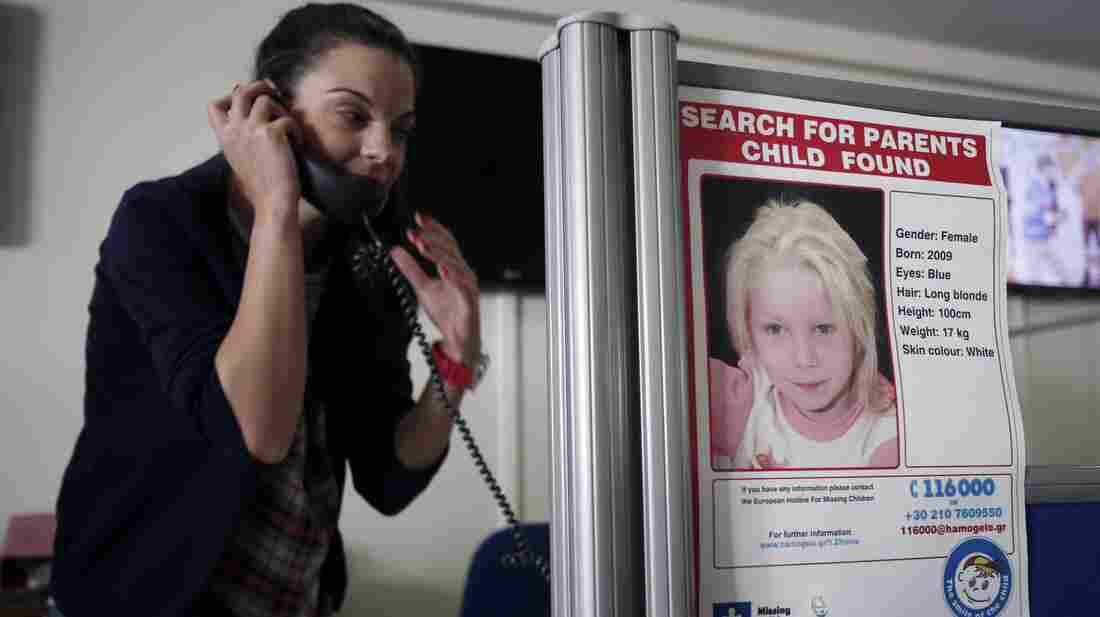 A woman takes a call at the Greek charity The Smile of the Child, which is caring for a girl who police say was abducted by a Roma couple. Officials are trying to find her biological parents.