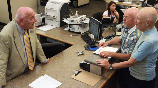 Dona Ana County Clerk Lynn Ellins talks with Thom Hinks and Richard Sunman (far right) after they obtained a marriage license at the Dona Ana County Clerk's Office in Las Cruces, N.M. In August, Ellins' office began issuing marriage licenses to same-sex couples.