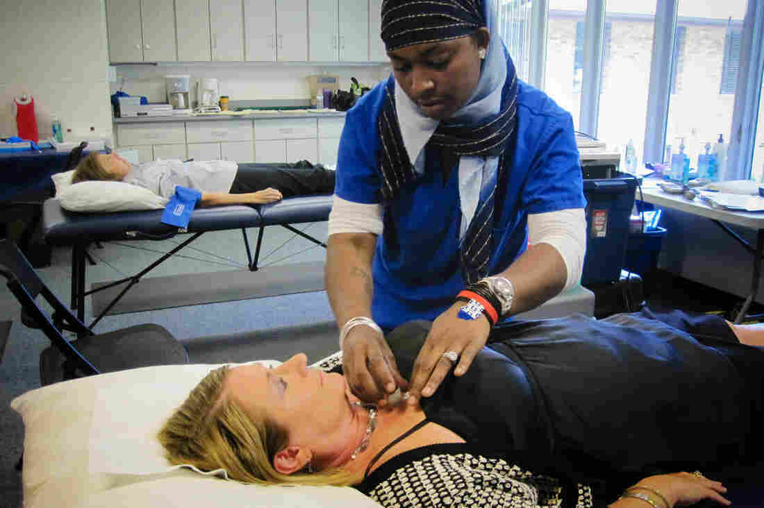 Stacy Riggs of Fairfax, Va., is prepped for a screening for atrial fibrillation by Life Line Screening medical assistant Kennea Blake at Messiah United Methodist Church in Springfield, Va.