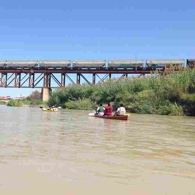 Kayakers head out on the Rio Grande toward one of the international bridges that connect Laredo, Texas, and the town of Nuevo Laredo in Mexico. Raw sewage and animal carcasses float in the water.