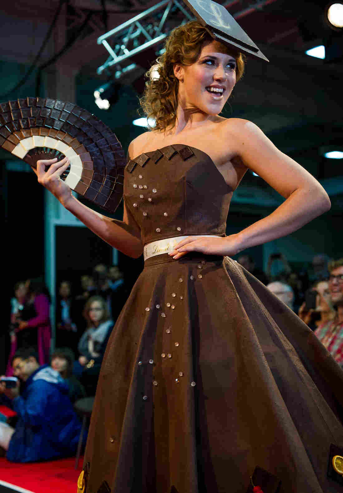 """Eternal Diamond,"" an A-line dress hand-painted with 40 pounds of Lindt chocolate. It's adorned simply along the hem with chili and orange segments, flavors used in speciality Lindt chocolate bars. The fan and hat are also crafted from chocolate, of course."