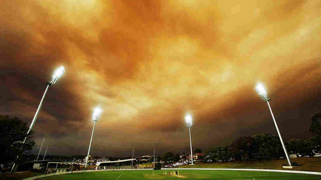 A general view of play as the Sydney skyline is shrouded in smoke during the Ryobi Cup match