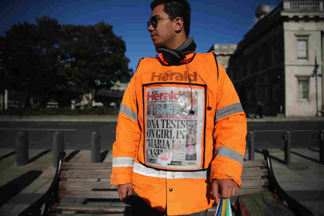 A newspaper vendor wears a vest displaying front page of The Herald on Wednesday in Dublin. Irish authorities were waiting for DNA test results in relation to a girl removed by Gardai from a Roma family in Dublin, days after a similar case in Greece. The test showed the girl was the biological daughter of the Roma family.