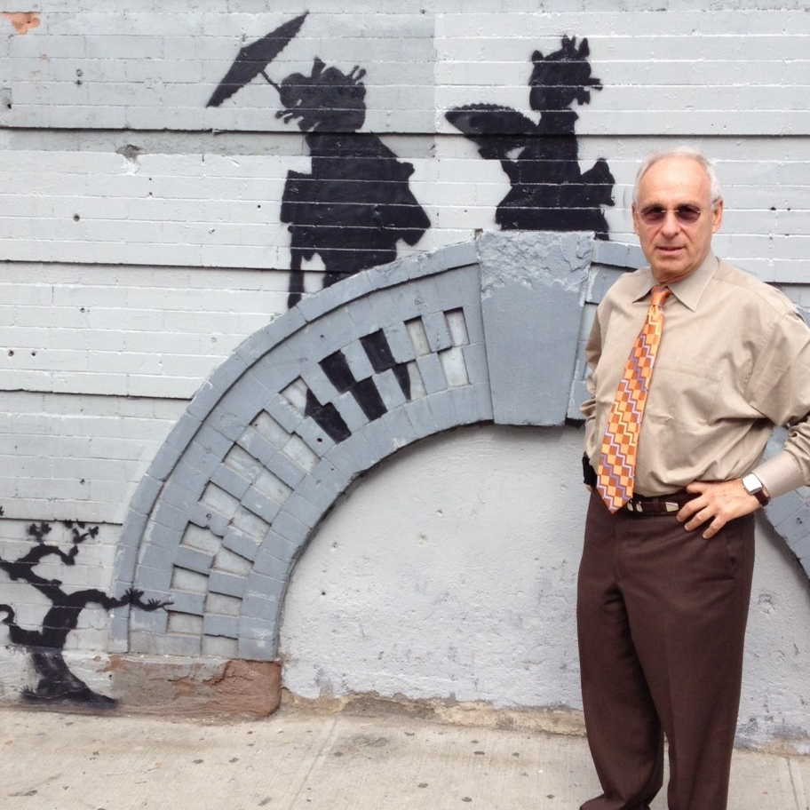 Cara Tabachnick's father stands next to Banksy's 17th installment in a monthlong New York City residency, which happens to be on his building in East Williamsburg, Brooklyn.