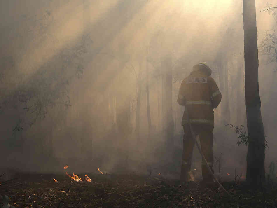 Flames flicker near Bilpin, Australia, as a firefighter finishes securing the area