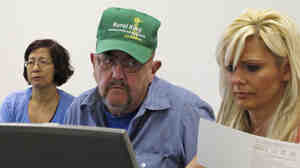 Patrick Lamanske, of Champaign, Ill., works with Amanda Ziemnisky (right), of the Champaign Urbana Public Health District, to try to sign up his wife, Ping, for health coverage through the Affordable Care Act on Oct. 1.