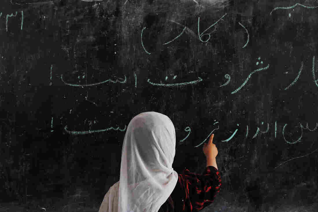 An Afghan child writes on a blackboard at a school built by German troops in a refugee camp on the outskirts of Mazar-e-Sharif. The number of students enrolled in Afghan schools has skyrocketed since the fall of the Taliban at the end of 2001.