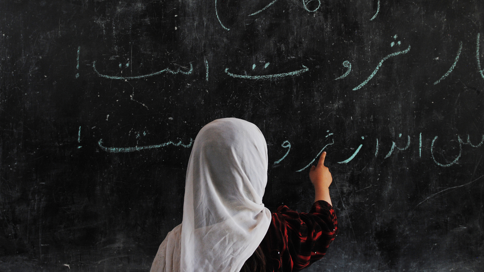 An Afghan child writes on a blackboard at a school built by German troops in a refugee camp on the outskirts of Mazar-e-Sharif. The number of students enrolled in Afghan schools has skyrocketed since the fall of the Taliban at the end of 2001. (AFP/Getty Images)