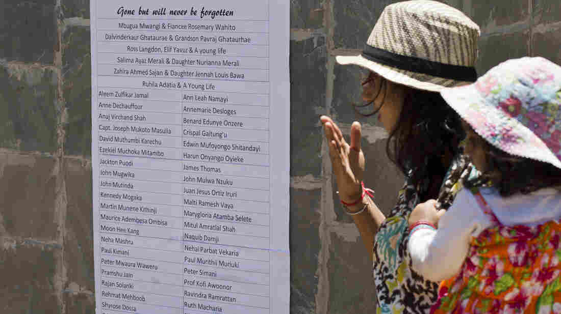 Relatives of Westgate attack victim Mitul Shah observe a list of names of some of those who died at a memorial service marking one month since the Sept. 21 terrorist attack in Nairobi, Kenya, on Monday.