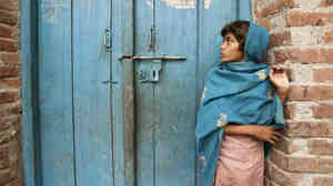 A young girl stands in the doorway of a home in Uttar Pradesh, India. The markings on the door show that a polio immunization team vaccinated children in the home.