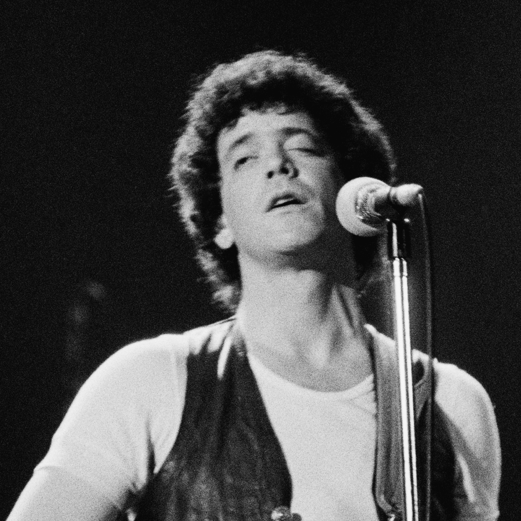 American rock singer-songwriter Lou Reed performs at the Hammersmith Odeon in London in 1975. He is playing a transparent, plexiglass guitar. Reed died Sunday at the age of 71.