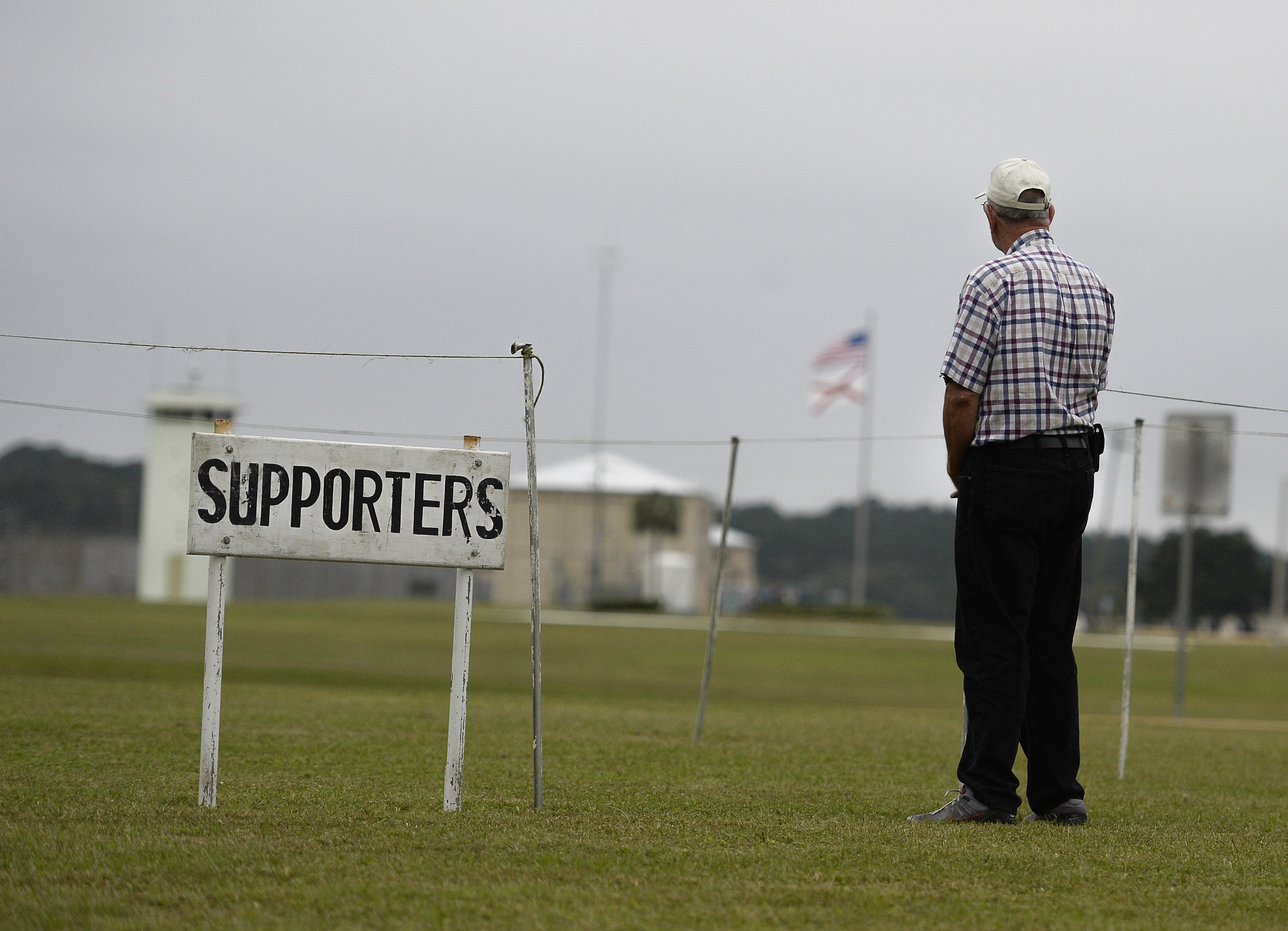 A lone supporter of the execution of William Happ stands across the highway from the Florida state correctional facility on Oct. 15. Happ was the first inmate to be put to death using the drug midazolam.