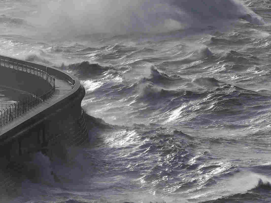 Waves produced by storm-force winds break against the harbor wall in Dover, England, on Monday.