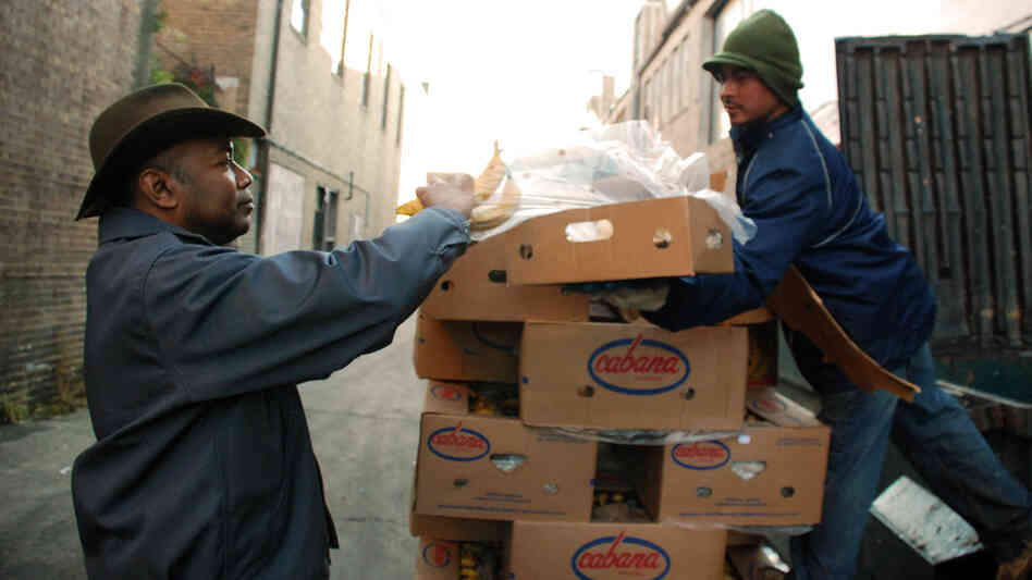 Roger Gordon (left) is offered a box of bananas from a worker who was throwing away the lightly speckled fruit at Mexican Fruits in Washington, D.C. Gordon's startup, Food Cowboy, works with truckers to divert edible produce from landfills to food charities.