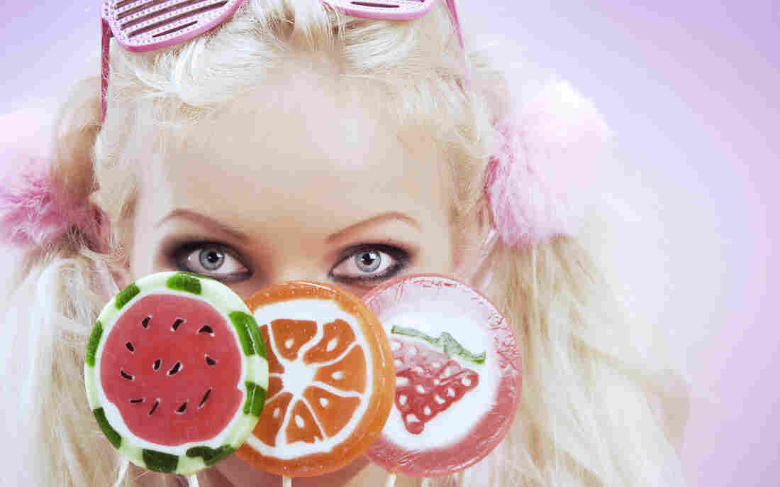 A blonde woman holding  colorful candy in front of her face.