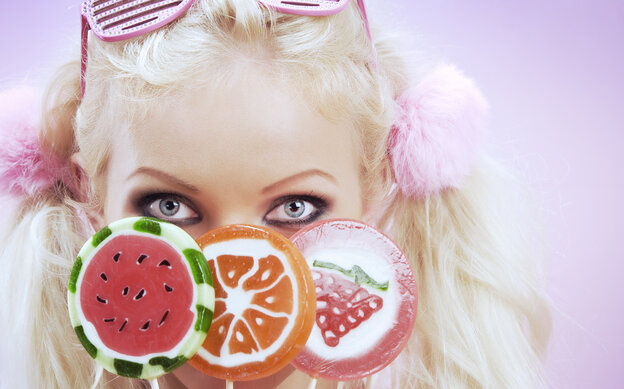 A blonde woman holding up colorful candy in front of her face.