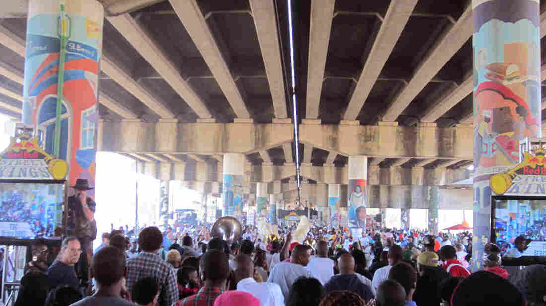 Spectators under the Clariborne Bridge in New Orleans' Treme neighborhood watch To Be Continued Brass Band parade into the judges area on Saturday.