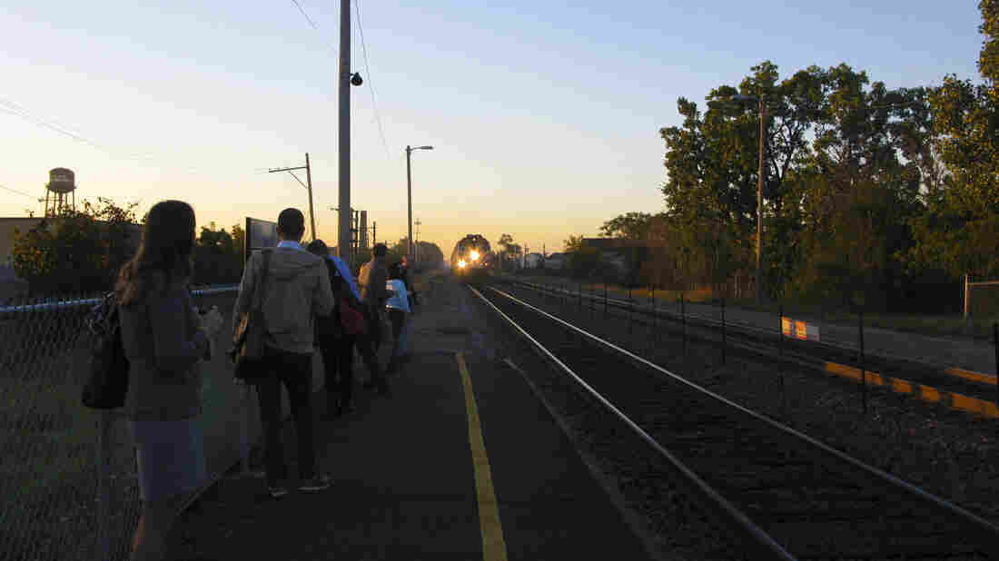 Reverse commuters, include Kathy LeVeque (in the foreground), wait for an approaching outbound Metra commuter train at the Mayfair neighborhood stop on Chicago's northwest side.