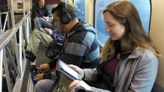 Kathy LeVeque reads her tablet on her reverse commute from her city home to her job in north suburban Deerfield.