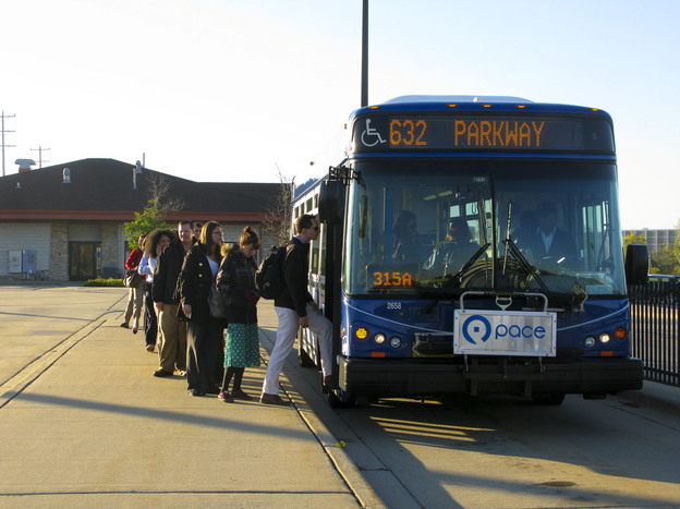 Commuters board shuttle buses at the Lake-Cook Metra rail stop in Chicago's northern suburbs. This Shuttle Bug program is a collaboration between area employers and the suburban transit agency, PACE, to provide better transit options for workers, especially those who live in the city but work in the Lake-Cook job corridor.